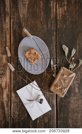 Top close up view of still life with handmade organic rustic soap with dried flowers soap-dish and little white cute romantic envelope on dark wooden table background. Vertical shot.