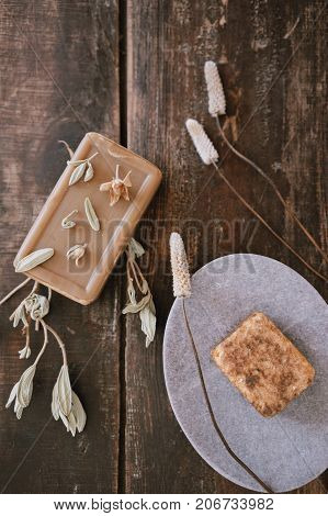 Top close up view of still life with handmade organic rustic soap with dried flowers marble or stone soap-dish on dark wooden table background. Vertical shot.
