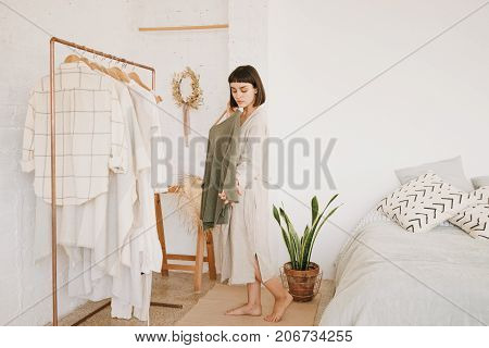 Attractive brunette young woman with short hair in linen beige robe at home standing in her white room in morning in front of rail with clothes and chooses green sweater to wear.