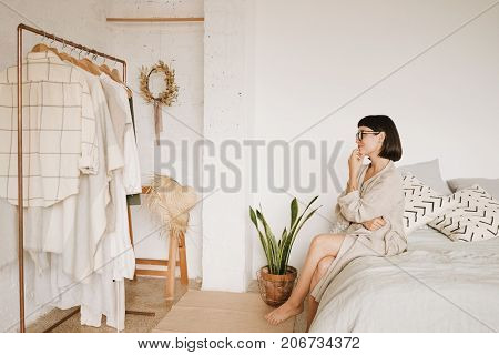 Young pretty lady with short black hair in glasses and linen beige robe sits on bed in morning in her big white room smiles and looks on her wardrobe thinking what to wear today. Space for text.