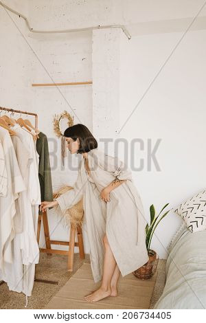 Attractive brunette young woman with short hair in linen beige robe at home standing in her white room in morning in front of rail with clothes and chooses outfit for day.