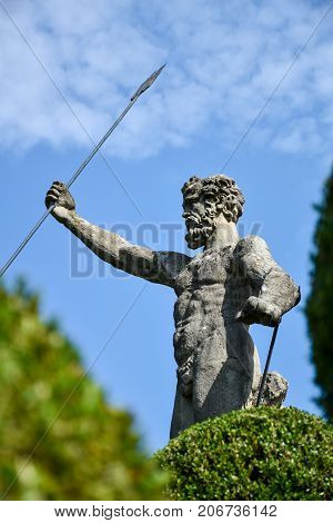 Statue of Neptune with a raised hand holding a trident in the gardens of Isola Bella in Lago Maggiore Italy