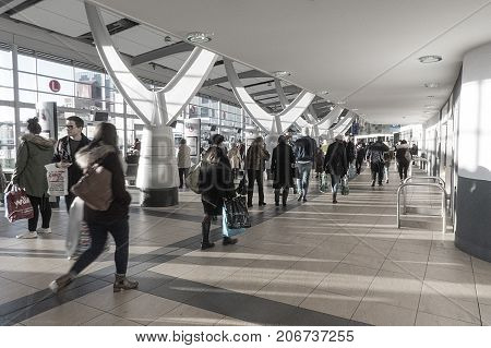 Swansea, UK: January 20, 2016: People walk through the Quadrant Centre Bus Station. The thirty year old building has recently been refurbished. Shopping bags have brand names advertising local shops.
