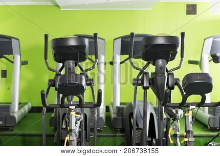 Treadmills and elliptical machines in a green walled gym
