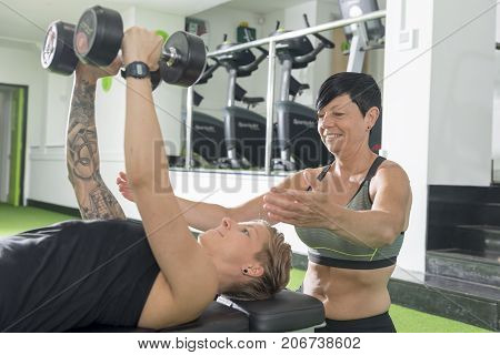 Personal Trainer Guiding Client Doing Dumbbell Bench Press In Gym