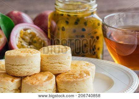 Homemade plain scones serve with homemade passion fruit jam and tea on wood table. Scones is English pastry for afternoon tea or cream tea. Delicious plain scones and homemade passion fruit jam ready to served with tea. Close up concept.