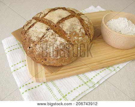 Homemade rye bread and rye flour in bowl
