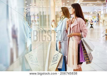 Side view portrait of two beautiful young women  in shopping center looking at window displays of store and smiling, choosing clothes