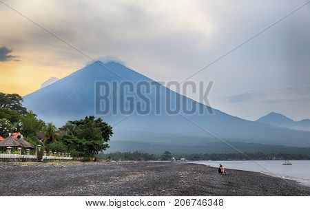 Bali. Beautiful landscape with views of the volcano Agung in Amed in the evening at sunset Indonesia. Volcanic black rocky beach at the foot of the volcano Agung. Nature Wallpaper