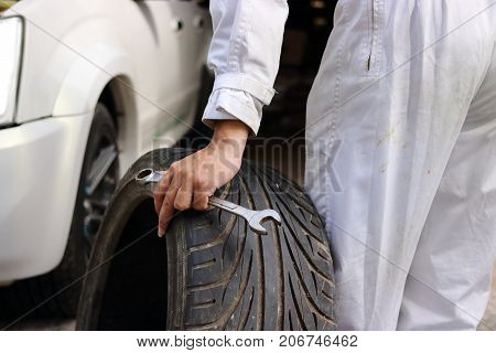 Hands of automotive mechanic in uniform with tire and wrench for fixing car at the repair garage background.