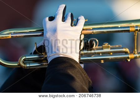 the gloved hands of a trumpet player in a marching band