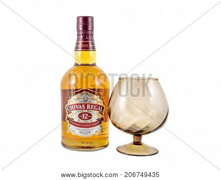 Ternopil Ukraine - August 26 2017: Bottle of Blended scotch whisky Chivas Regal. 12 years old scotch whiskey. Made in Scotland. Bottle of whisky with glass isolated on white.