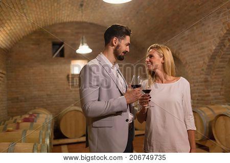 Wine loving couple tasting wines in winery cellar
