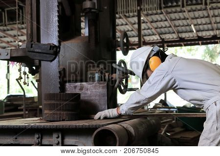Side view of young worker in uniform and safety equipment cutting a piece of wood on vertical band saw machine in carpentry factory.