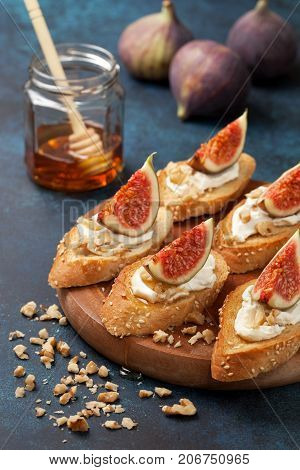 sandwiches with figs ricotta honey walnut fresh figs and a jar of honey on a blue background