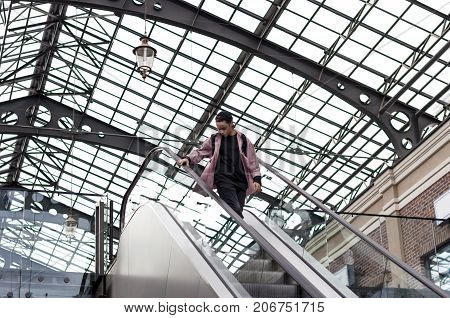 young man looking down standing on escalator steps