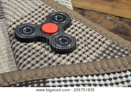 A Rare Wooden Handmade Spinner Lies On A Checkered Plaid On A Brown Wooden Background Surface. Trend