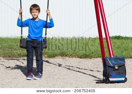 Tired boy after school sitting on the swing outdoors