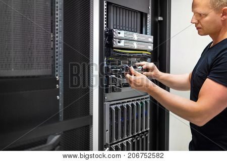 Confident mid adult male IT consultant monitors servers in data center