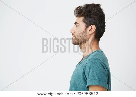 Half-face studio portrait of beautiful spanish man, in casual blue t-shirt, with trendy hair and beard, showing his profile and looking to the left. Copy space