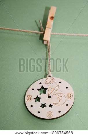 Wooden Christmas toy on a rope with a clothespin on a green background