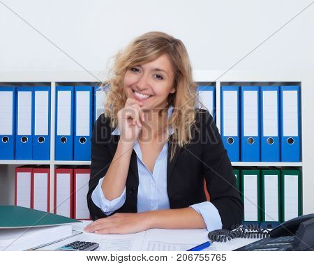 Businesswoman with curly blond hair laughing at camera