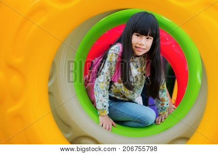 Asian kid fun and happy from play a donus ring in playgroung in her pre school outdoor kidchildren education concept