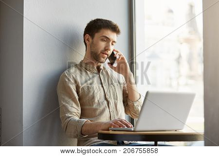 Unhappy handsome guy with dark hair, sitting in cafe, working on laptop computer and talking with dissatisfied customer on phone