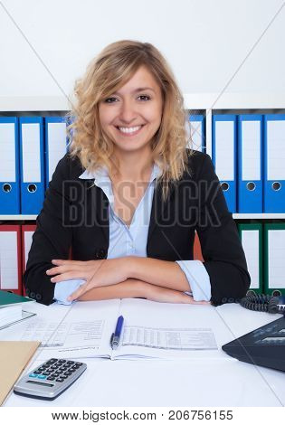 Attractive businesswoman with curly blond hair looking at camera
