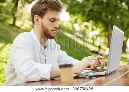 Attractive serious ginger european man in stylish clothes drinks coffee, intently working outside on his notebook, making design for a website