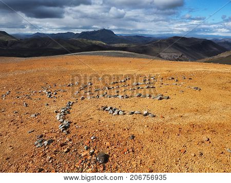 Figures lined with stones on the yellow surface of the mountain in the Landmannalaugar valley Iceland