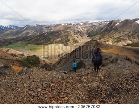 The hikers follow the path among the colored mountains in the Landmannalaugar valley Iceland