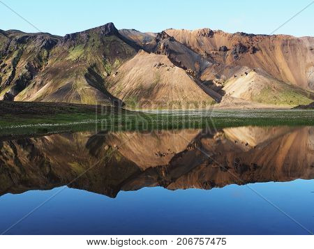 Colored mountains reflected in the lake in the Landmannalaugar valley Iceland