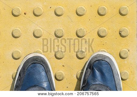 View from the First Person to his Feet Standing in Front of the Sidewalk with Tactile Tiles to Navigate Blind People. Blue Sneakers on Yellow Tactile Paving Slabs.