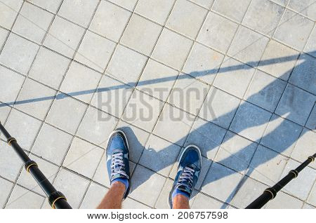 View from a tripod to the feet of a photographer taking pictures of the texture of paving stone. Blue Sneakers on a Gray Paving Sidewalk Top View.