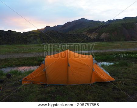 Tent against the background of the sunset and colored mountains in the Landmannalaugar valley Iceland