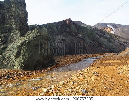 Creek flowing among yellow stones and greenish mountains in the Landmannalaugar valley Iceland
