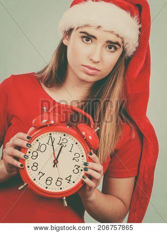 Sad Woman Wearing Santa Costume Holding Clock
