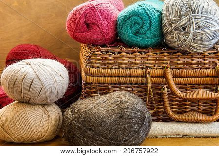 Vintage Crafts Wicker Chest Box Clews Balls of Colorful Wool Yarn Red Blue White Beige Grey Knitting Hobby Header Banner for Websites Close up