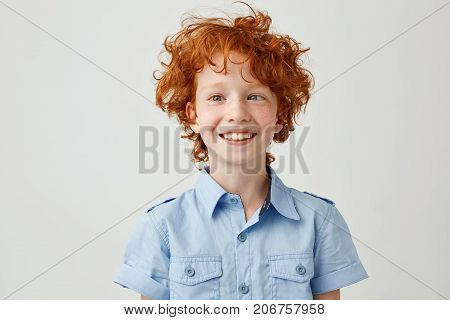Close up portrait of funny little boy with orange hair and freckles mowing eyes, smiling and making silly faces for school photo album.