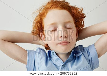 Close up of beautiful sleepy ginger boy with curly hair and freckles holding hands behind head with closed eyes being tired after school classes