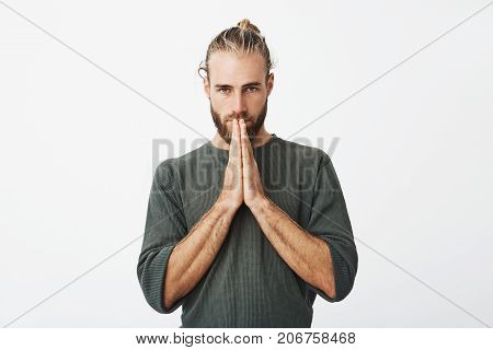 Please forgive me. Unhappy beautiful swedish man with sorrowful expression pressing hands together in front of him, asking a forgiveness from wife for hurting her feelings