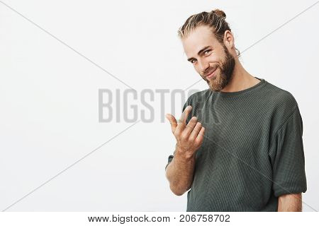 Handsome manly guy with beard saw beautiful girl staring ar him on the street and trying to beckon her with index finger with flirty expression