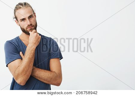 Portrait of attractive young man with stylish hairstyle holding hand on chin with thoughtful expression, looking in camera. Guy thinking about future life