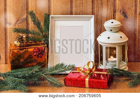 White photo frame lantern and christmas gifts on wooden table.