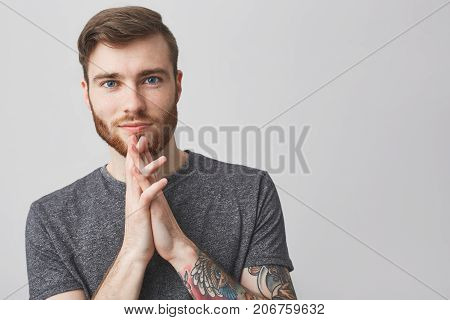 Close up portrait of beautiful happy caucasian man with beard, fashionable hairstyle and tattooed arm wearing grey shirt holding palms together near face, looking in camera with satisfied expression