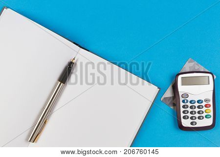 Electronic password generator for internet banking, payment card and open paper notebook with pen on blue background.