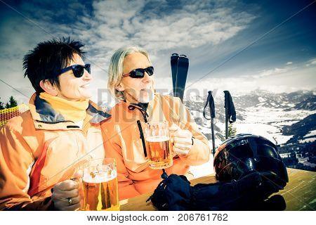 skiing senior couple having a break, enjoying a glass of beer