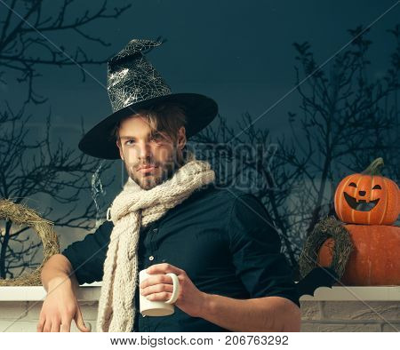 Halloween macho holding cup at window with autumn trees. Warm and homely atmosphere. Magic potion concept. Holiday symbols and decorations. Man wearing witch hat and scarf.