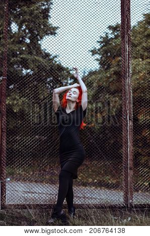 Redhead woman in black clothes holding grid in park. Closed eyes, push hands up.